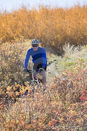 Man mountain biking in autumn