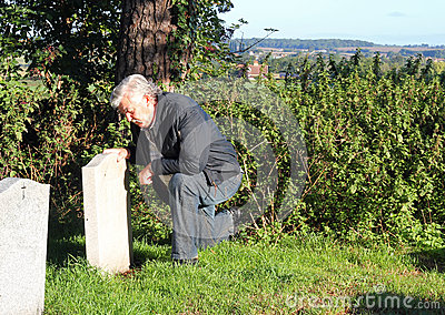 Man mourning at a cemetery.