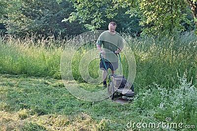 Man mowing tall grass