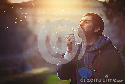 Man in nature. Harmony and romance. Dandelion blowing Stock Photo