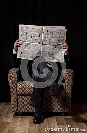 Man with newspaper sitting in vintage armchair