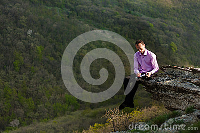 Man with notepad on stone