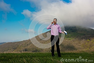 Man with notepad and telephone on mountain