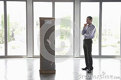 Man Observing Package In Empty Office