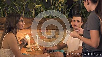 Man och kvinna som beställer mat för romantisk matställe med stearinljus i aftonrestaurang Servitris som tar beställning från lyc stock video