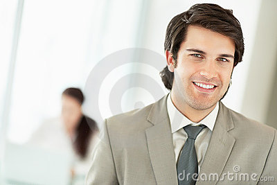 Man at the office with a colleague at the back