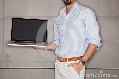 Man in office showing his presentation on laptop
