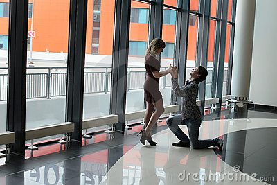Man on one knee before woman