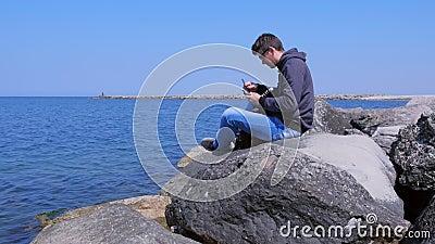 Man op zee neemt de rugzak telefoon met een driepoot om zelfgemaakte video op te nemen stock videobeelden