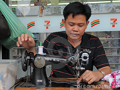 Man Operates Sewing Maching in Textiles Shop Editorial Stock Image