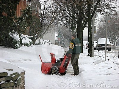 Man operating snow blower to clear driveway Editorial Image