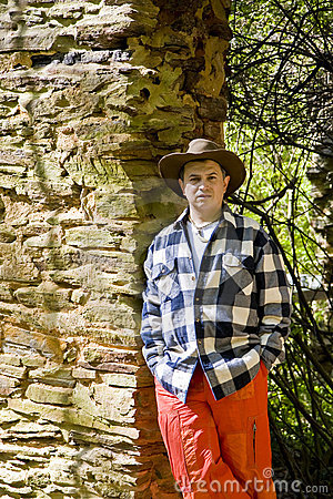 Man in Orange and Plaid on Rock Wall
