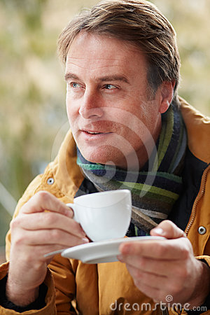 Man In Outdoor Cafe With Hot Drink