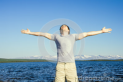 Man outdoor with his hands raised to the sky