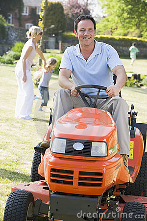Man outdoors driving lawnmower smiling with family
