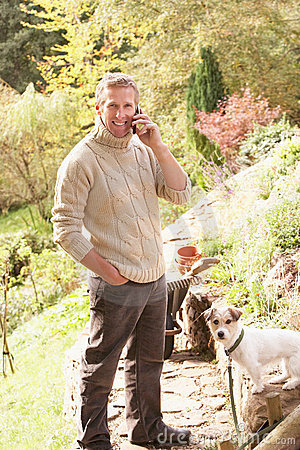 Man Outdoors On Mobile Phone With Dog
