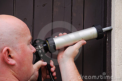 Man outside starting repair sealing house door