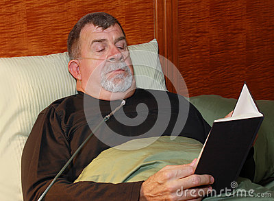 Man with Oxygen Cannula Reading in Bed
