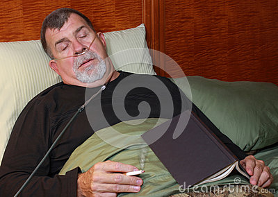 Man with Oxygen Cannula Smoking in Bed