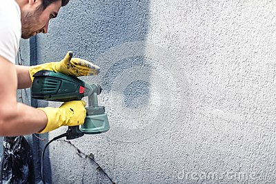 Man painting a grey wall renovating exterior walls of new for Time saver details for exterior wall design