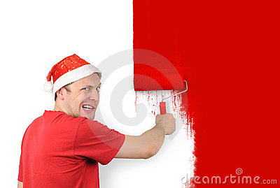 The man paints a wall roller brush with a red