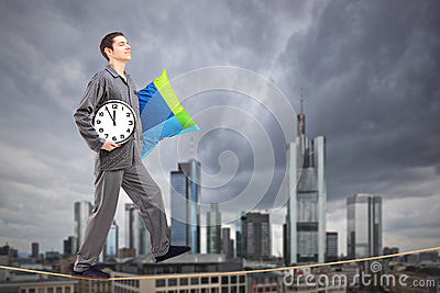Man holding a pillow and clock sleepwalking on a rope, with Fran