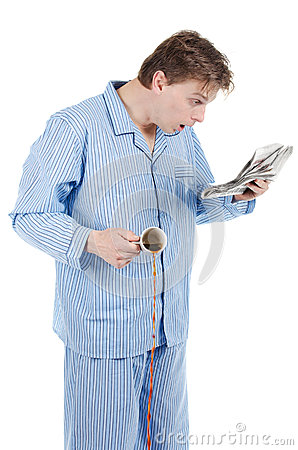 Man in pajamas reading newspaper