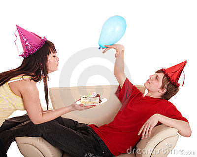 Man in party hat and girl eating cake.