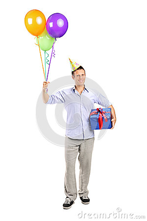Man with party hat holding balloons