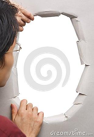 Man peeking through hole in wall