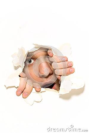 Man peeping through hole on paper