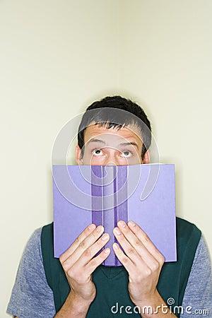 Man peering over top of book