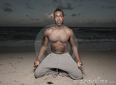 Man performing yoga on the beach