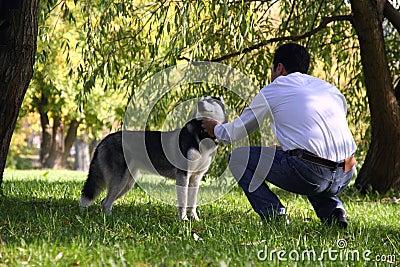 A man petting a husky dog