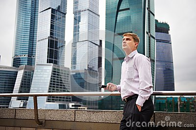 Man with phone against backdrop of city