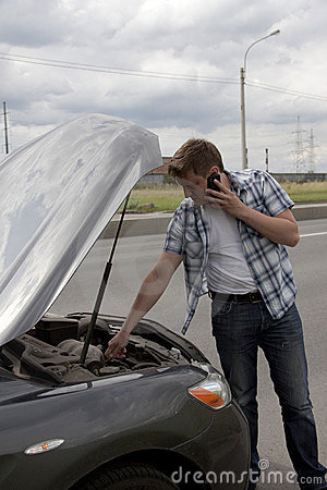 Man with phone beside his broken car