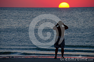 Man photographing a colorful ocean sunset