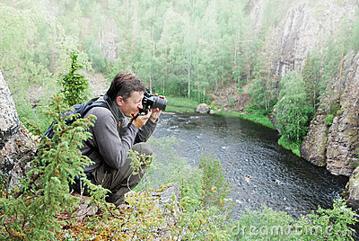 Man photographing on the top of taiga forest.