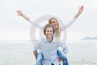 Man piggybacking woman at beach