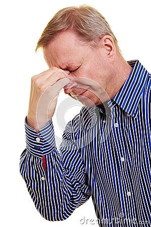 Man pinching back of his nose