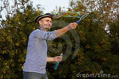 Man in pirate suit is blowing soap bubbles.