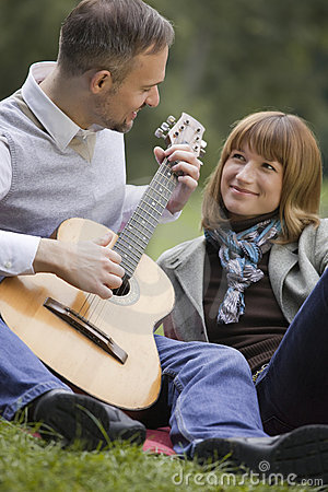 Man playing acoustic guitar outdoors