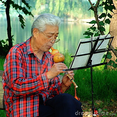Man Playing the cucurbit flute Editorial Image