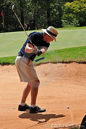 Man playing golf shot out of sand bunker on green