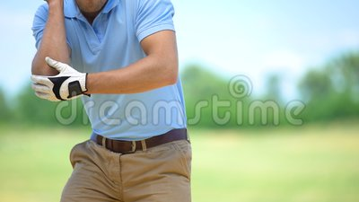 Man playing golf, suddenly feeling sharp elbow pain, massaging to relieve spasm. Stock footage stock video footage
