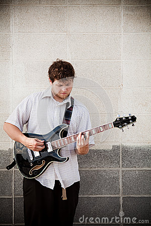 Man playing guitar against wall