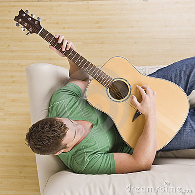 Man playing guitar on his couch.
