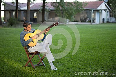 Man Playing Guitar in Lawn