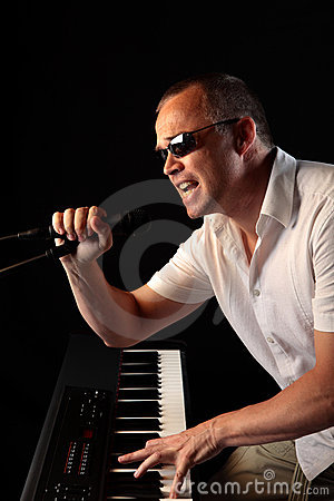 Man Playing Piano Singing into a Microphone
