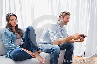 Man playing video games next to his annoyed partner
